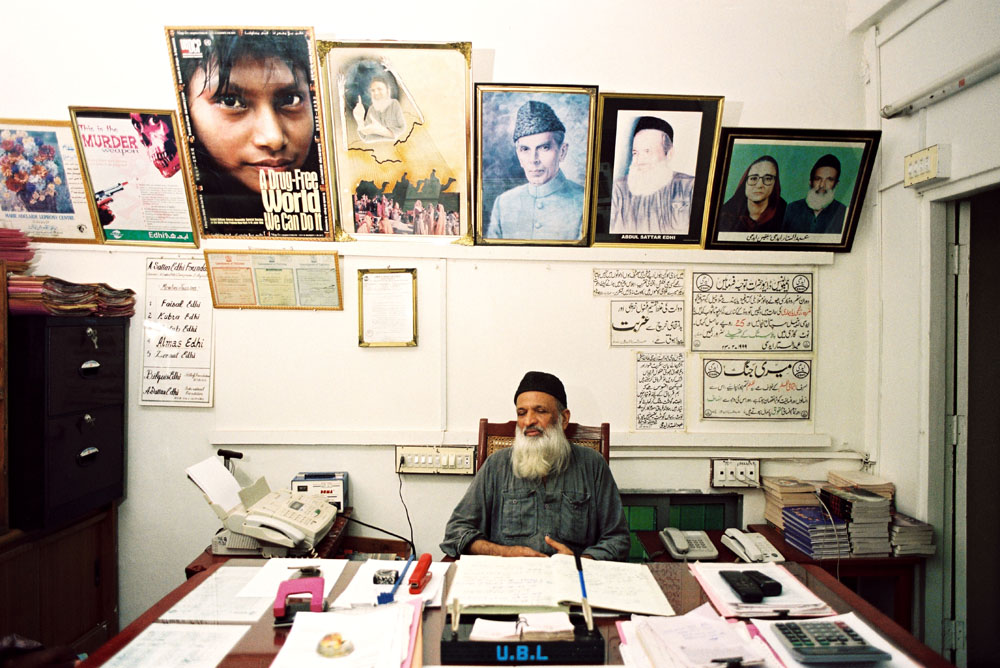 """Abdul Sattar Edhi sits at his desk in the Mithadar district of Karachi. His office is in the same building where, in 1951, he opened his first free pharmacy, and he remains personally on call: """"I am always available to all,"""" he says. Edhi may be the most widely admired man in Pakistan, yet he remains little known abroad: Starting in 1951 with a free pharmacy in a poor neighborhood of Karachi, Abdul Sattar Edhi has inspired-by deeds more than words-the growth of a vast nationwide Charitable organization of ambulances, clinics, orphanages, asylums, shelters, mortuaries, hospitals, schools and kitchens staffed today by more than 7000 volunteers and funded entirely by private donations. August 2004."""