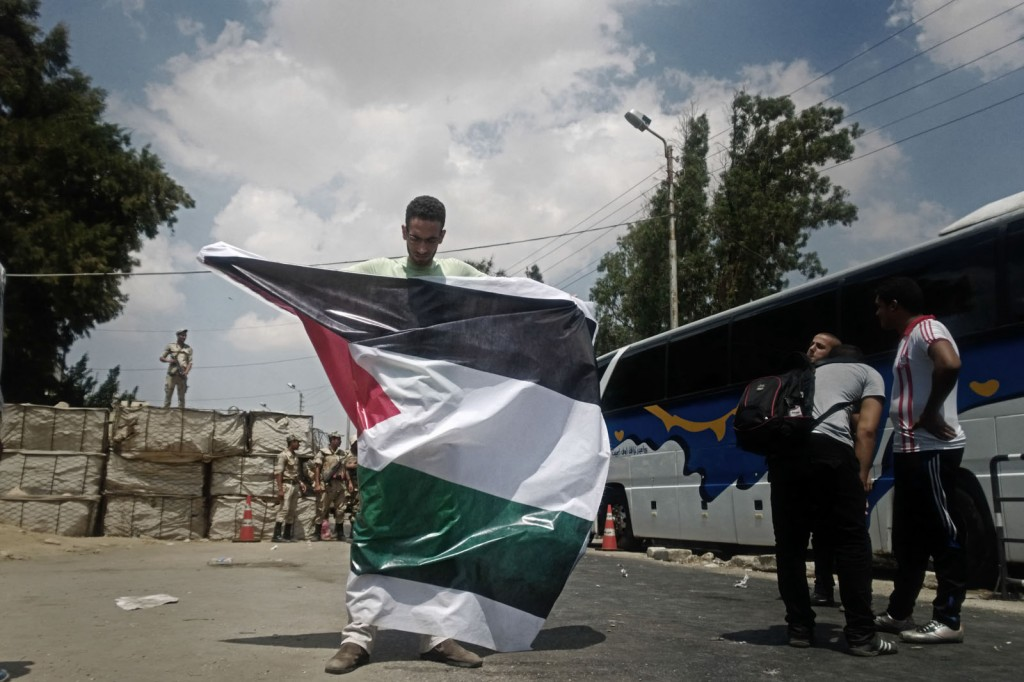 A volunteer holds the Palestinian flag at al-Balouza checkpoint.