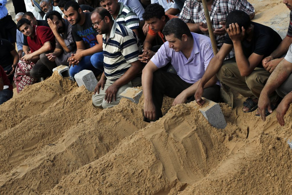 Mourners pray over the fresh graves of members of the Abu Jarad family who were killed in an Israeli strike on their family house, following their funerals in Beit Lahiya, in the northern Gaza Strip, Saturday, July 19, 2014. Eight members of the family were killed Friday night as a result of Israeli tank shelling on their home. Gaza Health Ministry spokesman Ashraf al-Kidra said the new round of strikes raised the death toll from the 12-day offensive to more than 330 Palestinians, many of them civilians. (AP Photo/Lefteris Pitarakis)