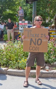 Atheist and Christians Hold Opposing Signs at the Bele Chere Fes