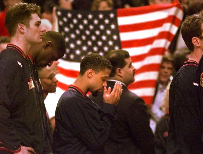 "Denver Nuggets guard Mahmoud Abdul-Rauf stands with his teammates and prays during the national anthem before the game with the Chicago Bulls on Friday night, March 15, 1996, in Chicago. Abdul-Rauf, saying that the U.S. flag was a symbol of ""oppression and tyranny,"" was suspended Tuesday for sitting down during the national anthem. Friday was Abdul-Rauf's first game back. The Bulls went on to beat the Nuggets 108-87. (Michael S. Green/AP)"