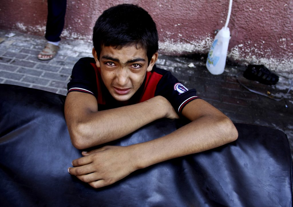 A Palestinian boy cries after watching his wounded relatives being rushed to emergency rooms at the Nasser hospital following an Israeli air strike in Khan Younis, the southern Gaza Strip, Thursday, July 24, 2014. Israeli troops backed by tanks and aerial drones clashed with Hamas fighters armed with rocket-propelled grenades and assault rifles on the outskirts of Khan Younis, killing many militants, according to a Palestinian health official. Hundreds of people fled their homes as the battle unfolded, flooding into the streets with what few belongings they could carry, many with children in tow. They said they were seeking shelter in nearby U.N. schools. (AP Photo/Hatem Ali)