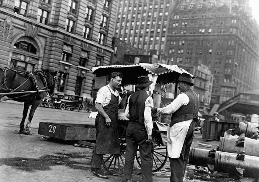 At a food cart in the streets of New York, a Syrian man peddles his food to a couple of hungry customers in the early 20th century. (Copyright Corbis/AP Images)
