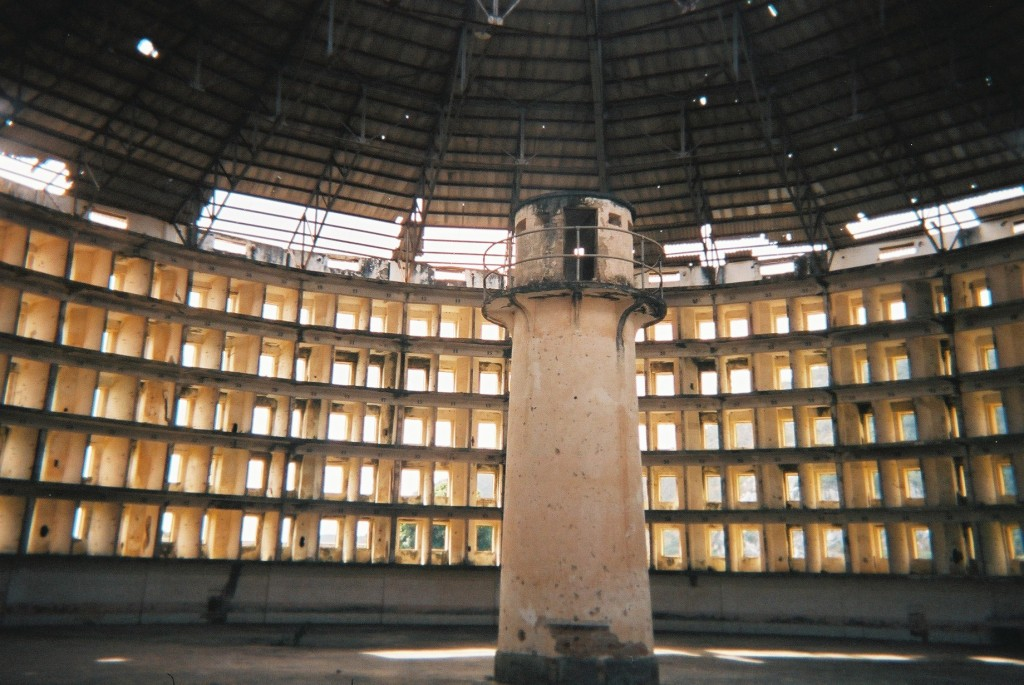 """The Panopticon is a type of institutional building designed by the English philosopher and social theorist Jeremy Bentham in the late 18th century.  the concept of the design is to allow a single watchman to observe (-opticon) all (pan-) inmates of an institution without the inmates being able to tell whether or not they are being watched.""""  Source wikipedia"""