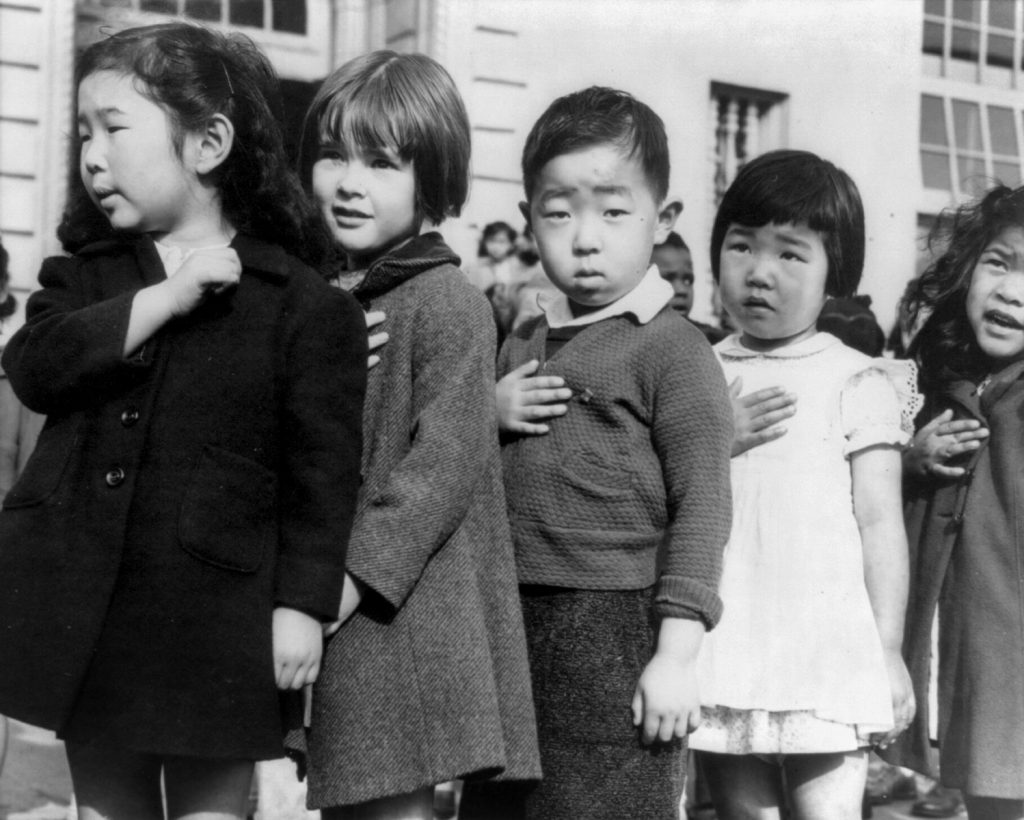 Children at the Weill public school in San Francisco pledge allegiance to the American flag in April 1942, prior to the internment of Japanese Americans. Source Wikipedia/CC