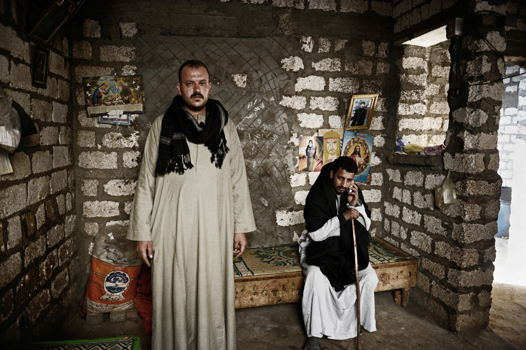 """Relatives of slain laborer Gerges Samir, 20 and Malak Ibrahim, 25.  Boules is their uncle (left) and Milad is their cousin who worked with Gerges and Malak in Libya and witnessed their abduction by ISIS (right). """"On the 28th of December 2014, we got a phone call from our friends informing us that they have been kidnapped - it was only 10 seconds. Later Gerges, Malak and I decided to go back to Egypt. A few days later Gerges and Malak were abducted by ISIS along with other 11 Egyptian Christians. That night, I heard gunmen stepping into their dormitory but I couldn't do anything. I was unarmed. Gerges travelled all the way to Libya to be able to pay for his brother's university. That is why his death was painful to his brothers more than any other person,"""" said Milad."""