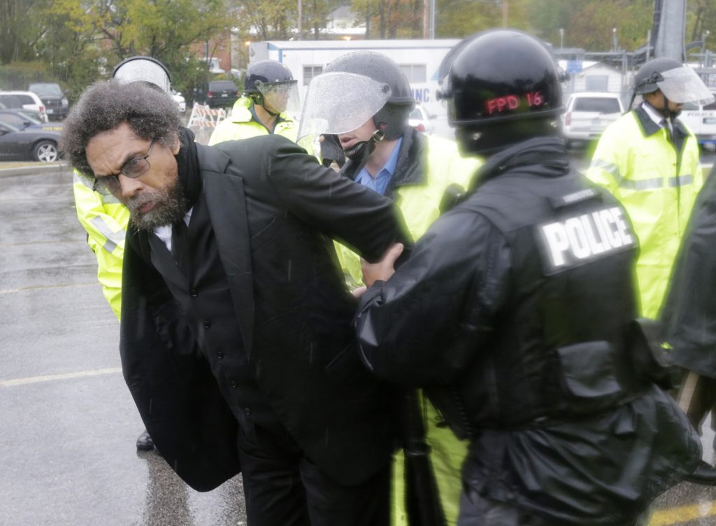 Philosopher Cornel West, center, is taken into custody after performing an act of civil disobedience at the Ferguson, Mo., police station Monday, Oct. 13, 2014, as hundreds continue to protest the fatal shooting of 18-year-old Michael Brown by police in August. In fact, tensions escalated last week when a white police officer shot and killed 18-year-old Vonderrit Myers Jr., who authorities say shot at police before he was killed. (AP Photo/Charles Rex Arbogast)