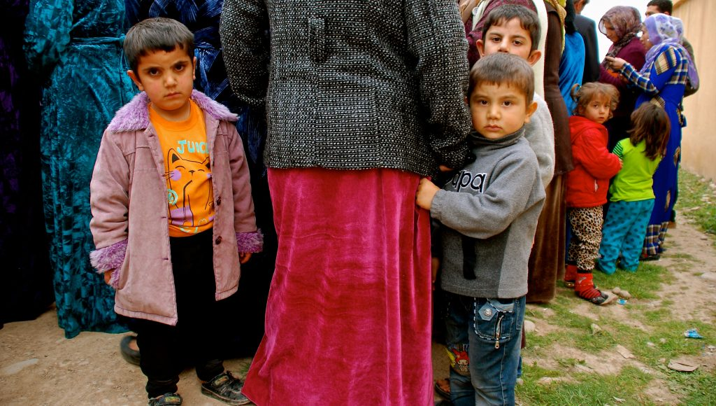 Small refugee children wait with their mothers as they line up to collect food and supplies from humanitarian organizations near Erbil.