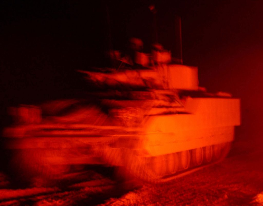 The iriee glow from the fire reflects off a  Bradley Fighting Vehicle from Apache Troop, 2-7 Cav, 2nd BCT, 1st Cav Div as it rolls back out to battle during combat operation in Fallujah on the 13th of Nov 2004 during Operation Iraqi Freedom. Photo by SFC Johancharles Van Boers, 55th Signal Company, Combat Camera, Fort Meade, Maryland. Release for Public Use