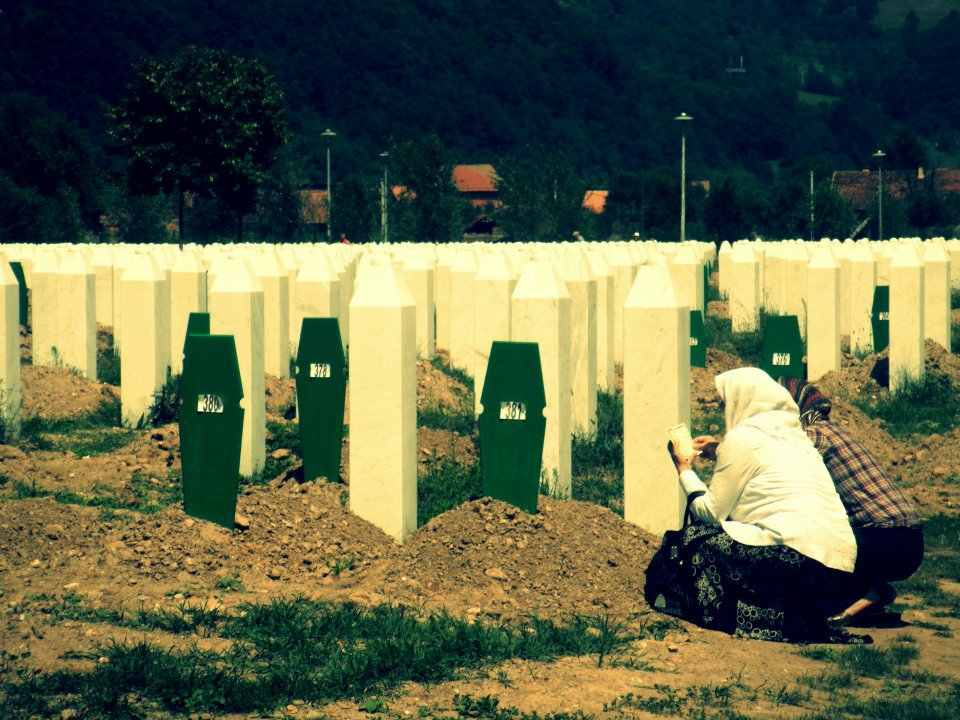 A mother praying at her son's grave.