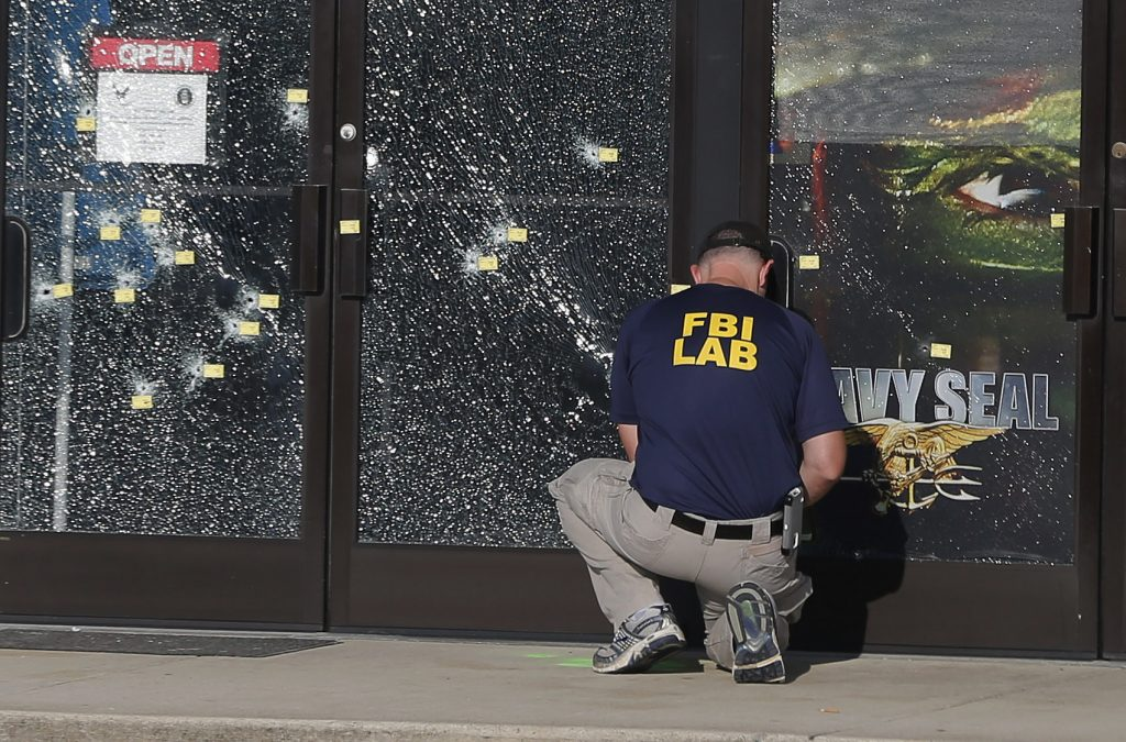 An FBI investigator works to gather evidence outside a military recruiting center on Friday, July 17, 2015, in Chattanooga, Tenn. Muhammad Youssef Abdulazeez of Hixson, Tenn., attacked two military facilities on Thursday, in a shooting rampage that killed four Marines. (AP Photo/John Bazemore)