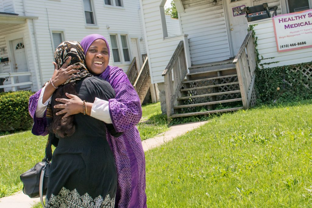 "Hanif welcomes a new resident to this home in Baltimore, Md. ""I like to call it a home, not a shelter,"" she says. Hanif has been striving for the past 27 years to provide a safe environment for Muslim women while empowering them through classes and programs. >Photos by Aeysha Chaudhry"