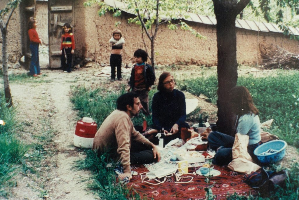 Powers spent her childhood years in the Middle East and Asia. Here are her parents, Richard and Helen Power, in a walled garden in Tehran, Iran. Carla's younger brother Nick stands with his arms crossed and Carla is standing on the left side of the door. >Photo courtesy of Carla Power