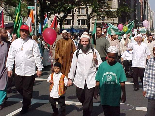A Muslim Day Parade with Yahya on the left with the red cap, the late Muhammad Mendez in the center, and right behind him in an olive polo shirt is Mustafa Rivera, Yahya's right hand muscle man.