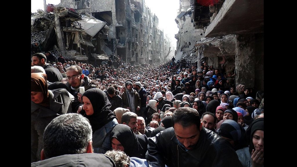 People line up for food at Yarmouk refugee camp. >Flickr/Jordi Bernabeu Farrús