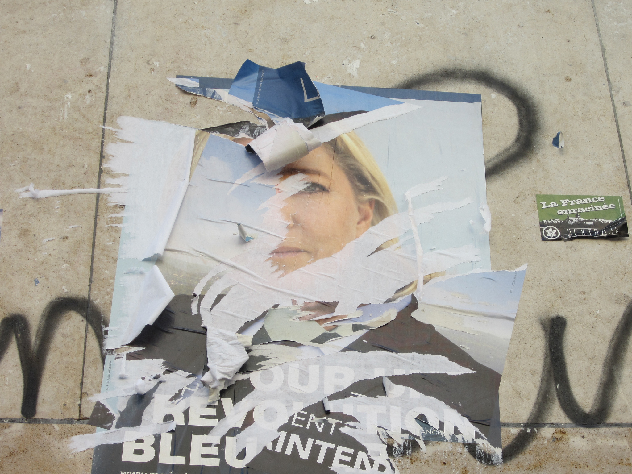 A torn up poster depicting Marine Le Pen, found in 2012. Photo Credit: Sylke Ibach Flickr Link: https://flic.kr/p/dBmjEG
