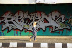 Caption: A woman walks past a wall of graffiti in Indonesia Credit: Budi Nusyirwan on Flickr Flickr URL: https://flic.kr/p/nUqk5P