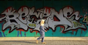 Caption: A woman walks past a wall of graffiti in Indonesia Credit: Budi Nusyirwan on Flickr Flickr URL: https://flic.kr/p/nUqk5P