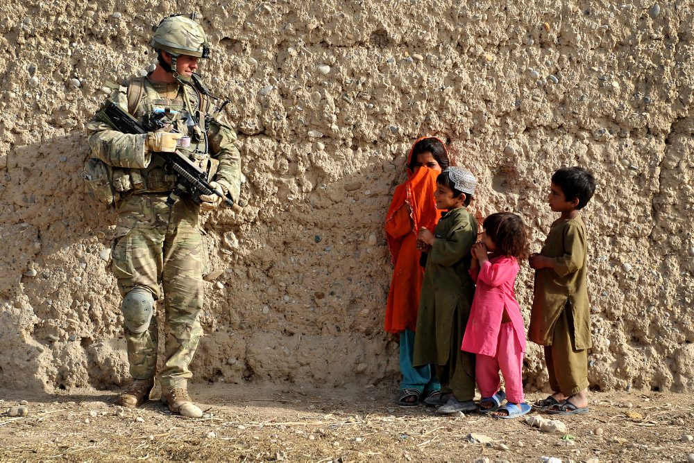 A Scottish soldier talks to local children. >Flickr/Defence Images